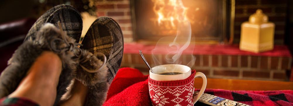 pessoa em frente a fogueira com cafe e controle
